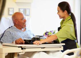 caregiver serving meal to elder man
