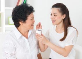 caregiver feeding elder woman