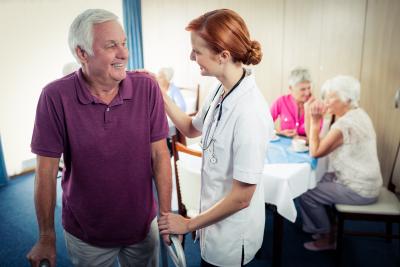 nurse assisting a senior using a walker
