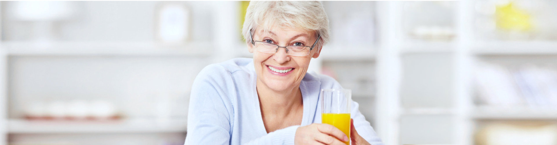 senior woman smiling holding a glass of juice