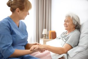 senior and nurse holding hands